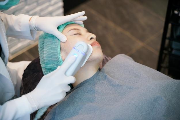 O procedimento de tratamento do elevador da face do aperto da pele do laser ou da freqüência envolve