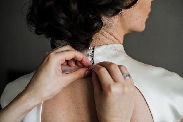 O processo de amarrar um vestido de noiva, vista traseira