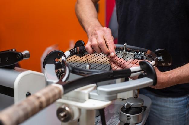 O processo de amarrar uma raquete de tênis em uma loja de tênis