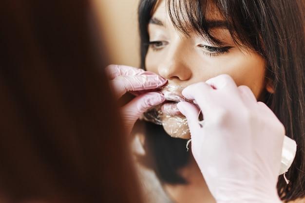 O processo de aplicação de analgésico nos lábios do paciente antes do realce dos lábios.