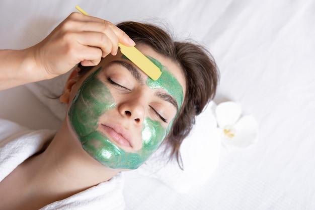 O processo de aplicação de uma máscara cosmética verde no rosto de uma jovem