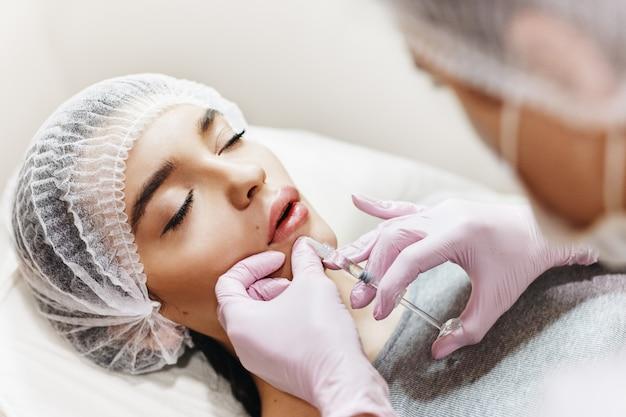 O processo de aprimoramento dos lábios. cosmetician faz uma injeção de ácido hialurônico nos lábios bonitos. a jovem garota com um rosto bonito no chapéu especial e nas mãos do médico na luva rosa