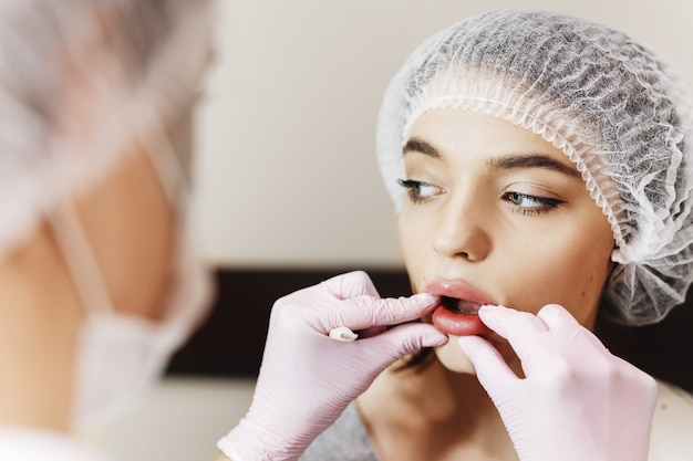 O processo de aprimoramento dos lábios. o médico analisa os lábios melhorados. a jovem com um rosto bonito no chapéu especial e as mãos do médico em luvas cor de rosa.