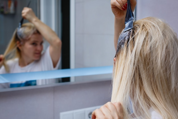 O processo de coloração de cabelo, coloração de cabelo, coloração de cabelo em andamento, mulher obtém nova cor de cabelo, coloração de cabelo em andamento