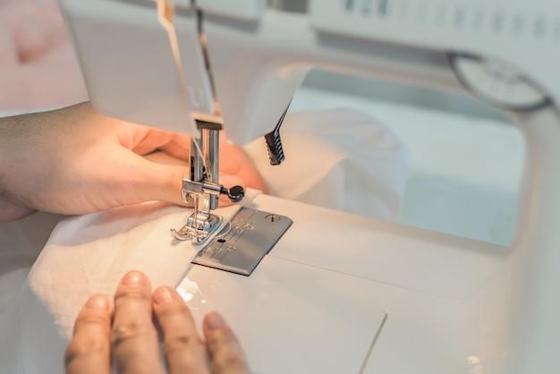 O processo de costura de roupas, mãos na máquina de costura, tecido branco de costura