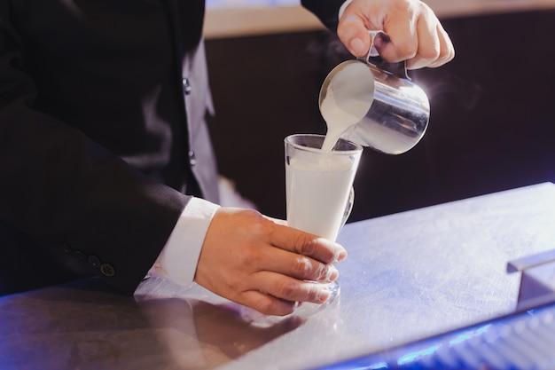 O processo de derramar espuma de leite na fabricação de café.