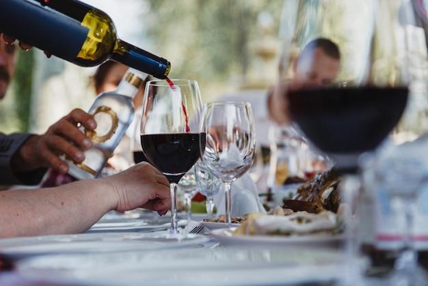 O processo de derramar vinho tinto em um copo. festa pública ao ar livre
