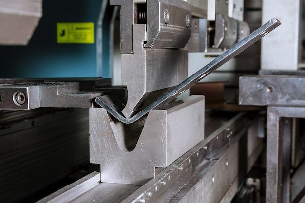O processo de dobrar chapas de metal em uma máquina de dobra hidráulica. planta metalúrgica.