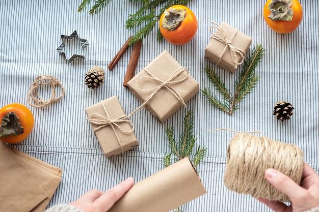 O processo de embalagem de presentes modernos e elegantes para o natal e o ano novo. caixas para presente em papel kraft, barbante e galhos de árvores de natal. fundo de natal, atmosfera de férias.