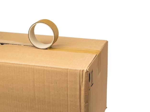 O processo de embalar uma caixa de papelão usando fita adesiva isolada em uma superfície branca