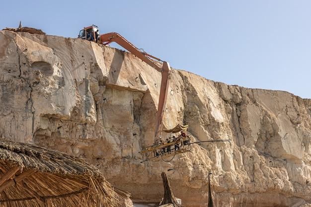 O processo de extração de rochas de um penhasco no egito.