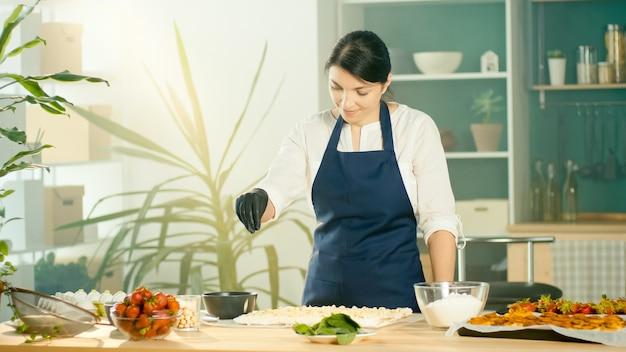 O processo de fabricação de produtos de confeitaria. o chef polvilha o bolo com nozes. interior moderno e aconchegante da cozinha. conceito de fabricação de confeitaria e pequenos negócios.
