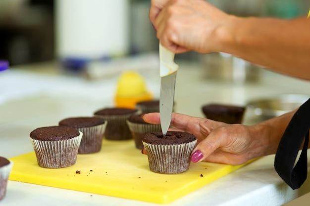 O processo de fazer cupcakes de chocolate com creme doce. criação de bolos por chefs de pastelaria profissionais