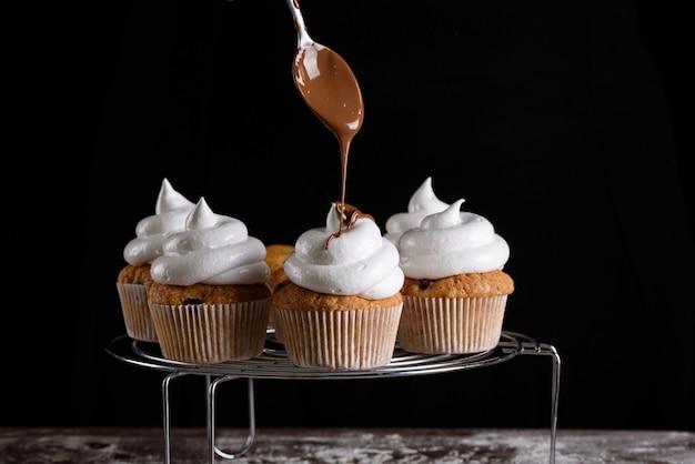 O processo de fazer cupcakes, revestir um creme de um saco de confeitar nas mãos de um confeiteiro.