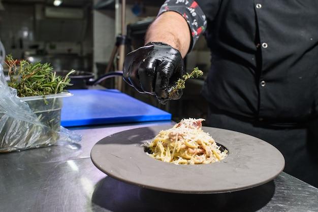 O processo de fazer macarrão carbonara para clientes de restaurantes. comida saborosa.
