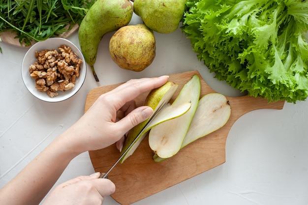 O processo de fazer uma salada de dieta leve com rúcula e pêra. a mulher corta a pêra em uma placa de madeira sobre uma mesa branca. vista de cima. foto de alta qualidade