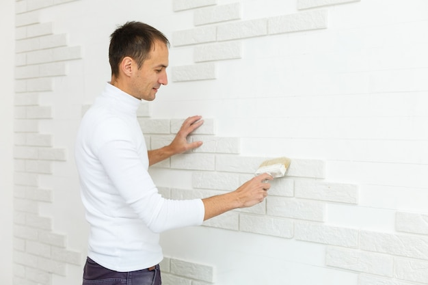 O processo de instalação de ladrilhos decorativos de arenito na fundação da casa