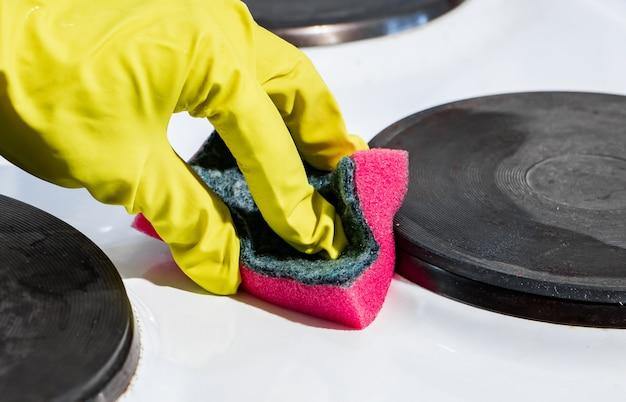 O processo de lavar um fogão elétrico. uma mão em uma luva amarela limpa a superfície branca da sujeira.