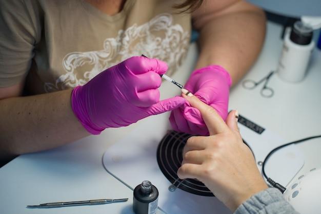 O processo de manicure feminino em um salão de beleza, esmaltes em gel.
