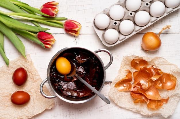 O processo de pintura de ovos de páscoa com corantes vegetais naturais, cascas de cebola, em uma vista superior do fundo de madeira branco de ovos de galinha e tulipas vermelhas.