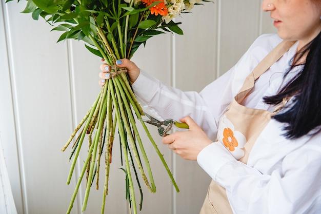 O processo de poda das hastes de um buquê com tesouras de poda em uma floricultura