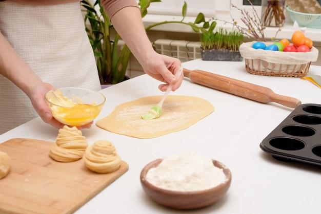 O processo de rolar a massa em casa sobre a mesa está nas mãos de uma mulher para fazer bolinhos festivos de cruffins para a páscoa