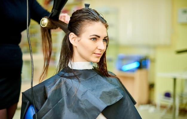 O processo de secar o cabelo de um jovem