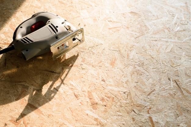 O processo de serrar madeira compensada com uma serra elétrica, um homem segura uma ferramenta na mão.