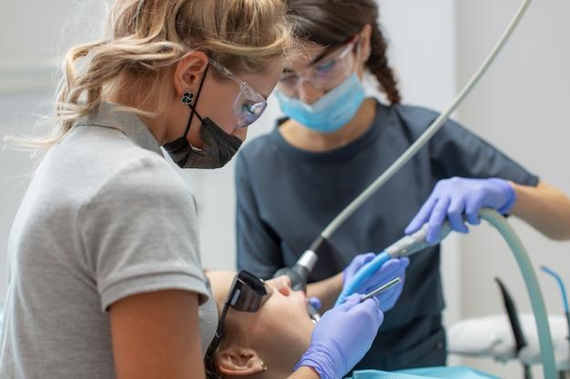 O processo de tratamento de cárie em uma clínica odontológica.