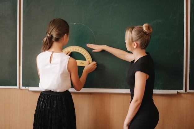 O professor ajuda a garota pelo quadro-negro. estudo de jovem professora