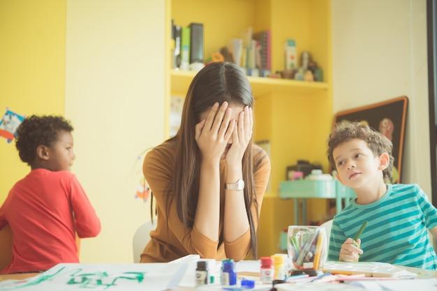 O professor asiático das mãos do jardim de infância fechou os dois ouvidos dela em um aborrecimento de não conseguiu reprimir o romance travado, dos meninos na sala de aula em crianças pré-escolares. imagens de estilo de efeito vintage.