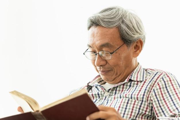 O professor asiático dos vidros do ancião aprecia ler o livro de texto cada conceito do dia.