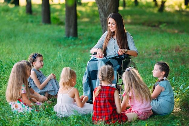 O professor com deficiência conduz uma lição com as crianças da natureza. interação de um professor em cadeira de rodas com os alunos.