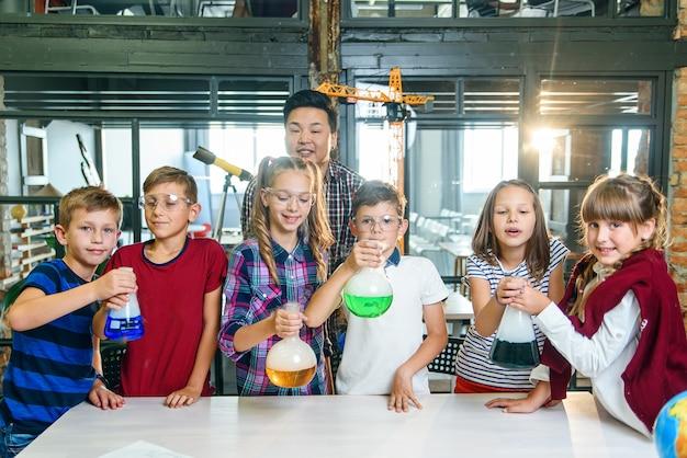 O professor coreano com um grupo de seis alunos caucasianos jovens alegres que usam óculos de proteção durante o experimento químico na escola moderna segura o vidro de teste com líquido colorido.