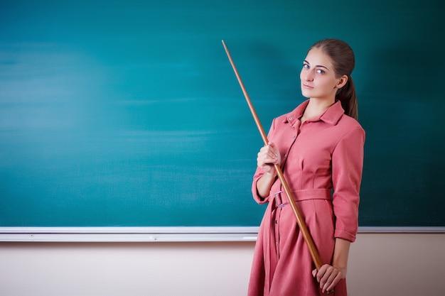 O professor da jovem mulher está em um quadro-negro com um ponteiro. dia do professor.
