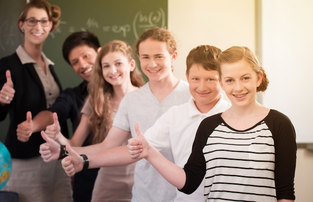 O professor da turma e os alunos ficam em frente a um quadro-negro com trabalhos de matemática em uma sala de aula durante a aula