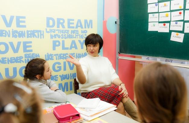 O professor em sala de aula ensina inglês aos alunos.