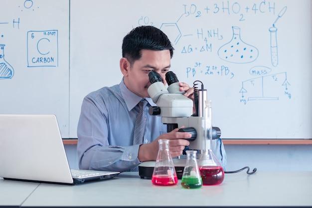 O professor está dando aulas de ciências online durante o bloqueio devido à pandemia de covid-19 com o uso de computador e microscópio em sala de aula