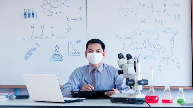O professor está dando aulas de ciências online durante o bloqueio devido à pandemia de covid-19 com uso de máscara facial