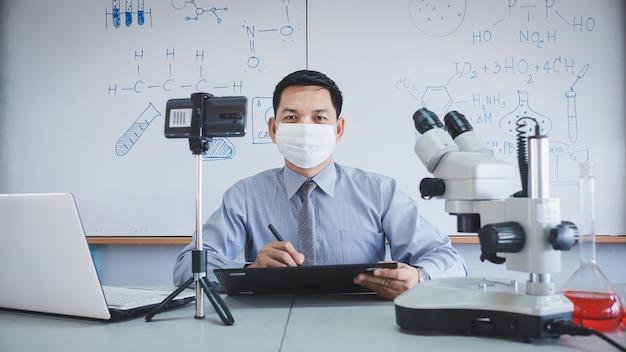 O professor está usando máscara facial e dando aulas de ciências online com smartphone durante o bloqueio devido à pandemia de covid-19