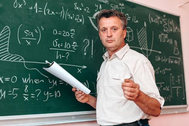O professor que está em seguida um quadro-negro e explica uma lição que prende um livro de texto.