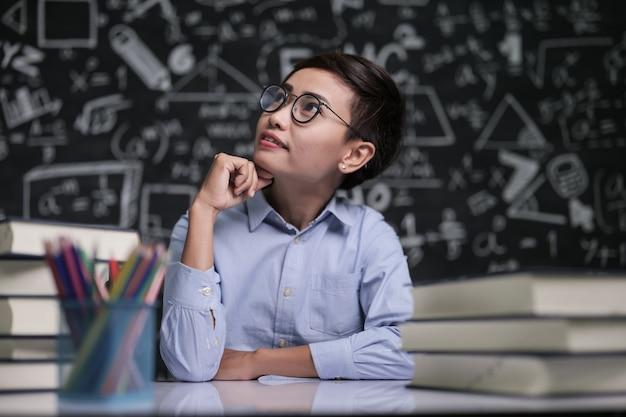 O professor sentou pensando em ensinar em sala de aula