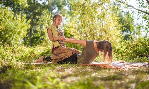 O profissional de massagem demonstra métodos de massagem refrescantes ao ar livre.
