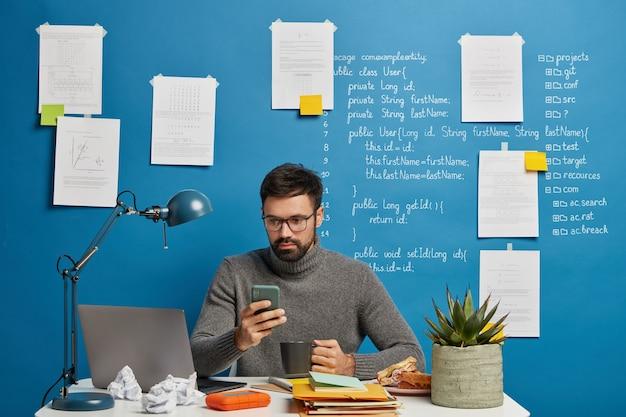 O profissional de ti trabalha no projeto de inicialização, atualiza o software e o banco de dados no celular, bebe uma bebida quente, senta na mesa contra a parede azul com informações escritas.