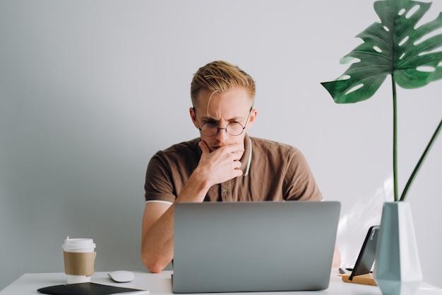 O programador desenvolvedor móvel escreve o código do programa em um laptop no escritório doméstico