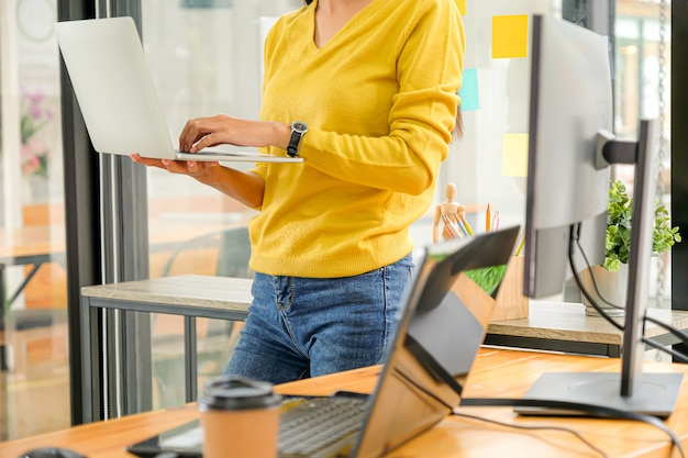 O programador está de pé, carregando e usando um laptop para testar o sistema no escritório.