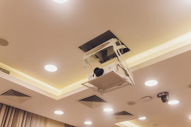 O projetor velho e sujo pendura no teto na sala de reuniões, conceito da educação.