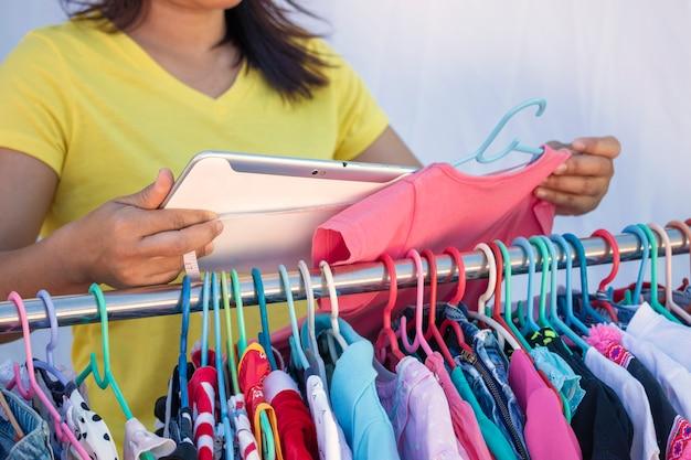 O proprietário da loja de roupas infantis usa o tablet para apresentar o modelo ao cliente.