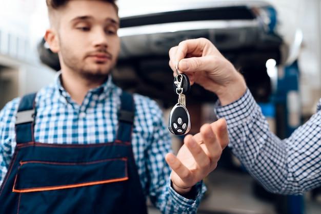 O proprietário de carro dá chaves ao auto mecânico na garagem.