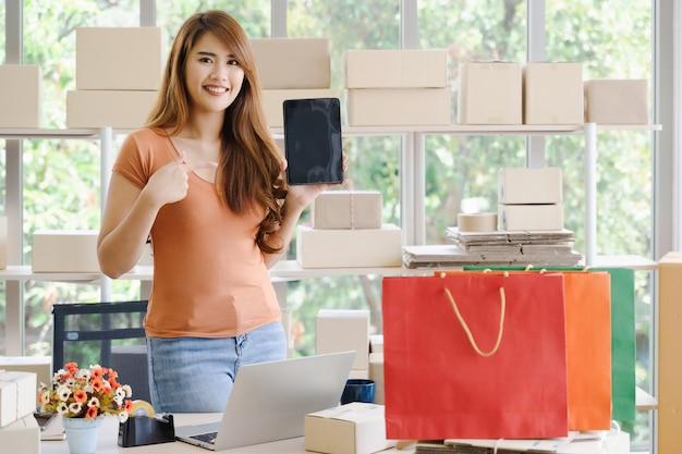 O proprietário de mulher de negócios asiáticos feliz linda jovem da pme on-line está de pé e apontando para tablet ou smartphone em seu escritório em casa inicialização com caixa de embalagem e sacolas de compras, compras on-line